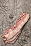 Fette di lardo del bacon della pancia di carne di maiale sulla vecchia superficie di legno annodata della Tabella Fotografia Stock