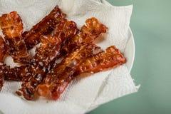 Fette di lardo fritte croccanti del bacon che vuotano sul piatto con il tovagliolo sul fondo pastello di verde della menta immagine stock libera da diritti