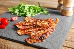 Fette di lardo fritte del bacon sul piatto dell'ardesia immagini stock libere da diritti