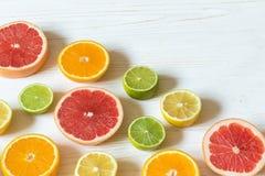 Fette di limone, di arancia, di limetta e di pompelmo sulla linguetta di legno bianca Fotografia Stock