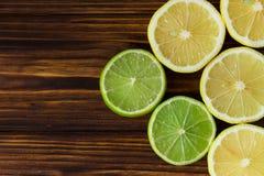 Fette di limoni e di limette freschi sulla tavola di legno marrone Reticolo Immagine Stock