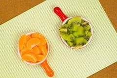 Fette di mandarino in una tazza rossa Fette di tazza dell'arancia del kiwi Fotografie Stock
