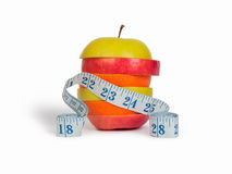 Fette di mele ed arancio e un nastro di misurazione Fotografia Stock Libera da Diritti