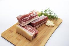 Fette di pancia di carne di maiale con aglio e le erbe su un tagliere Fette succose di carne con bacon con pepe immagini stock