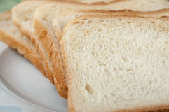 Fette di pane del pane tostato su una zolla bianca Fotografia Stock Libera da Diritti