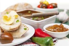 Fette di pane e di burro con i pomodori, i peperoni, il chutney e la p Immagine Stock