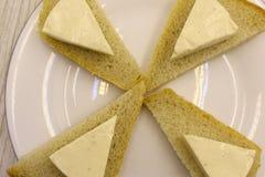 Fette di pane nero con i semi di sesamo ed il formaggio sui vecchi precedenti di legno fotografia stock