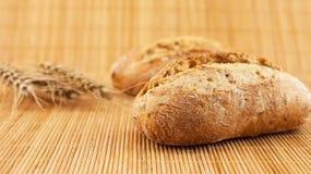 Fette di pane organico decorate con i cereali naturali su fondo e su grano di legno Fotografia Stock