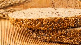 Fette di pane organico decorate con i cereali naturali su fondo e su grano di legno Immagini Stock
