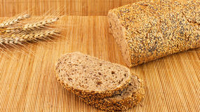 Fette di pane organico decorate con i cereali naturali su fondo e su grano di legno Fotografie Stock Libere da Diritti