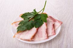 Fette di petto e di prezzemolo in piatto sulla tavola di legno immagine stock