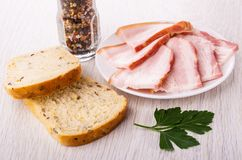 Fette di petto in piatto, pane, prezzemolo, barattolo con il condimento sulla tavola immagini stock