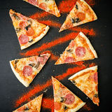 Fette di pizza italiana con salame sulla tavola scura Modello delle fette della pizza Disposizione piana, vista superiore Immagini Stock