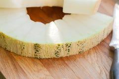 Fette di primo piano e di coltello del melone che si trovano su un bordo di legno fotografia stock