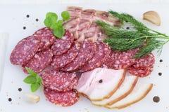 Fette di salame, di bacon, di spezie e di verdi su fondo bianco Fotografia Stock