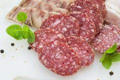 Fette di salame e di bacon su un fondo bianco Immagini Stock