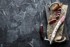 Fette di salame francese del saucisson su un fondo grigio Fotografia Stock