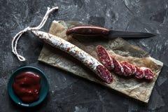 Fette di salame francese del saucisson su un fondo grigio fotografia stock libera da diritti