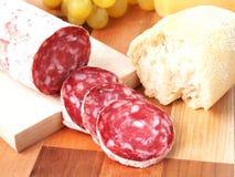 Fette di salame italiano sul tagliere Immagini Stock