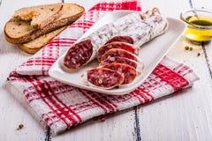 Fette di salame su un piatto bianco Fotografia Stock Libera da Diritti
