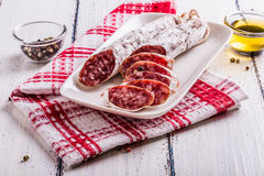 Fette di salame su un piatto bianco Fotografie Stock Libere da Diritti
