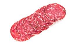 Fette di salsiccia del salame su un fondo bianco Immagini Stock Libere da Diritti