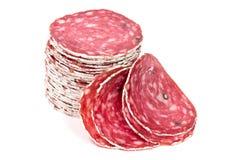 Fette di salsiccia del salame su un fondo bianco Fotografie Stock Libere da Diritti