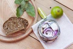 Fette di sgombro marinato con la cipolla in un barattolo, in una calce, in un alloro ed in un pane Fotografia Stock