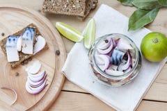 Fette di sgombro marinato con la cipolla in un barattolo, in una calce, in un alloro ed in un pane Fotografie Stock