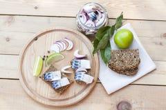 Fette di sgombro marinato con la cipolla in un barattolo, in una calce, in un alloro ed in un pane sul bordo di legno Immagine Stock