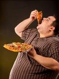 Fette Fleisch fressende Schnellimbissscheibenpizza Frühstück für übergewichtigen Menschen Stockbilder
