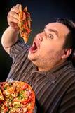 Fette Fleisch fressende Schnellimbissscheibenpizza Frühstück für übergewichtigen Menschen Stockfoto