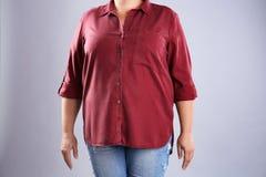 Fette Frau auf grauem Hintergrund, Nahaufnahme stockfotografie
