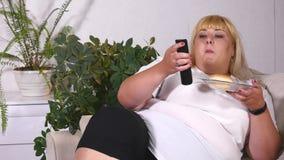 Fette Frau, die einen Burger, ein aufpassendes Fernsehen und laughes isst Stockbilder