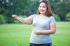 Fette Frau, die ihren Magen misst Stockfotografie