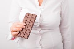 Fette Frau, die Schokolade isst Lizenzfreie Stockfotos