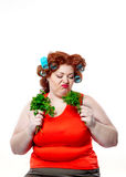 Fette Frau mit rotem Lippenstift der Sinnlichkeit in den Lockenwicklern auf Diät, die Petersilie und Dill halten Lizenzfreies Stockbild