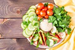 Fette fresche di cetrioli, pomodori, semi di sesamo in una ciotola Fotografia Stock Libera da Diritti