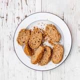 Fette fresche di intero pane nero su un piatto bianco su briciolo rustico Fotografia Stock