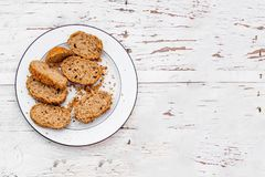 Fette fresche di intero pane nero su un piatto bianco su briciolo rustico Immagini Stock
