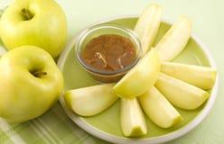 Fette gialle del Apple con il tuffo della caramella Fotografie Stock