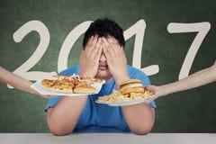 Fette Person mit ungesunder Fertigkost und 2017 Stockbild