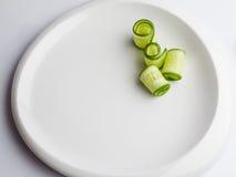 Fette rotolate del cetriolo sul piatto bianco Fotografie Stock