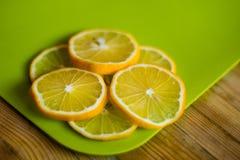 Fette rotonde del limone su un tagliere verde su una tavola di legno fotografia stock libera da diritti