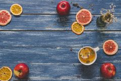 Fette secche dell'agrume con la tazza di tè e delle mele sulla tavola di legno blu, vista superiore Copi lo spazio Immagine Stock