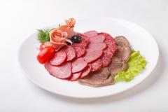 Fette sottili di salsiccia e di carne su un fondo di bianco del piatto Fotografie Stock Libere da Diritti
