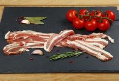 Fette, spezia e pomodoro crudi del bacon sul bordo nero Fotografie Stock Libere da Diritti