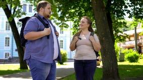 Fette sprechende und lächelnde Hochschulstudenten, romantisches Datum im Park, Freundschaft stockfotografie