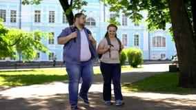 Fette Studenten, die in den Campuspark und -unterhaltung, flirtend auf Datum, Freundschaft gehen lizenzfreies stockfoto
