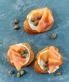 Fette tostate del pane con formaggio cremoso ed il salmone fotografie stock libere da diritti